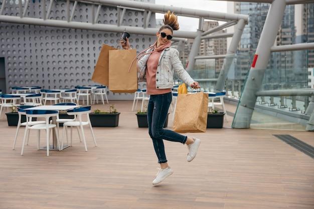 Mulher jovem feliz, segurando a xícara de café, pulando com um saco de papel com baguete de pão branco