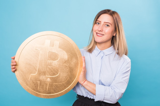 Mulher jovem feliz segurando bitcoin dourado, piscando, pensando em criptomoeda.