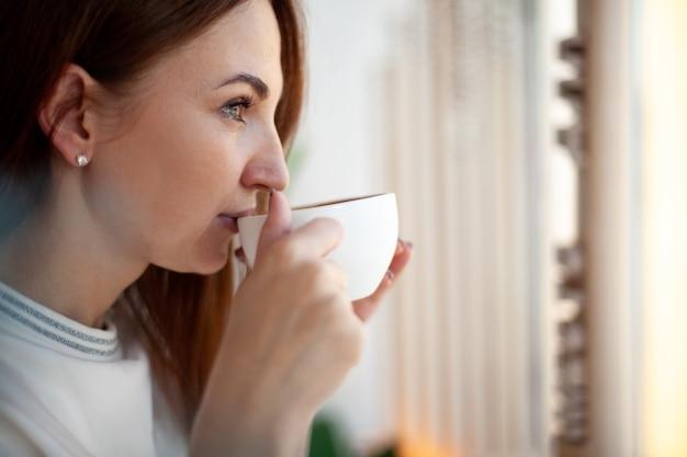 Mulher jovem feliz segurando com as mãos uma xícara de café com leite quente e saudável