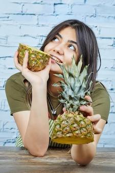 Mulher jovem feliz segurando duas metades de abacaxi.