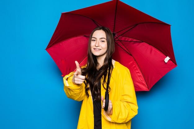 Mulher jovem feliz segurando guarda-chuva com capa de chuva amarela e parede azul
