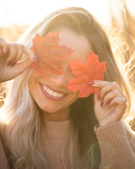 Mulher jovem feliz segurando maple folhas e cobrir os olhos ao ar livre