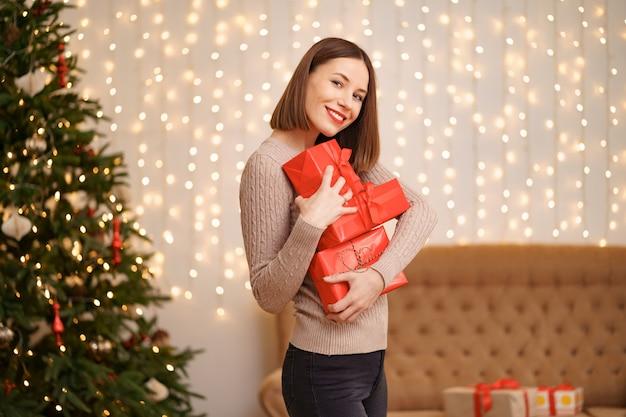 Mulher jovem feliz segurando muitas caixas de presentes com luzes e árvore de natal