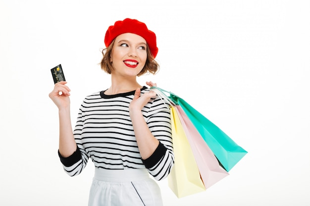 Mulher jovem feliz, segurando o cartão de crédito e sacolas de compras
