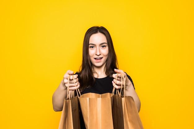 Mulher jovem feliz segurando sacolas de compras em uma parede amarela
