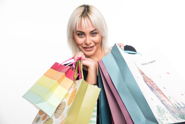Mulher jovem feliz segurando sacolas de compras no fundo branco. foto de alta qualidade