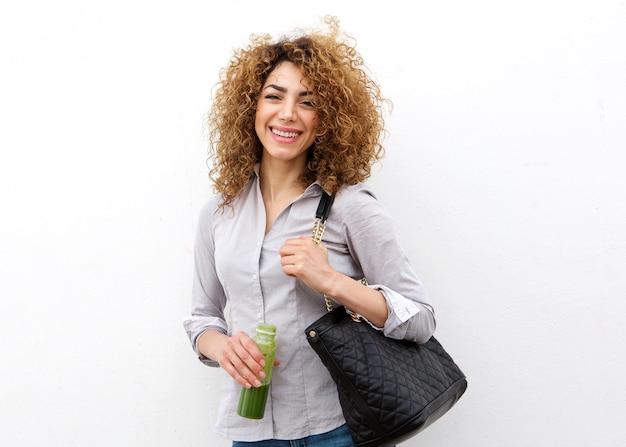 Mulher jovem feliz segurando suco beber pela parede branca