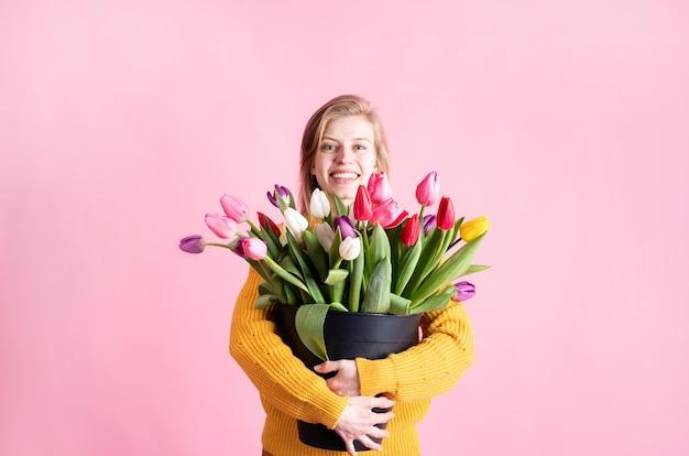 Mulher jovem feliz segurando um balde de tulipas frescas isoladas em um fundo rosa