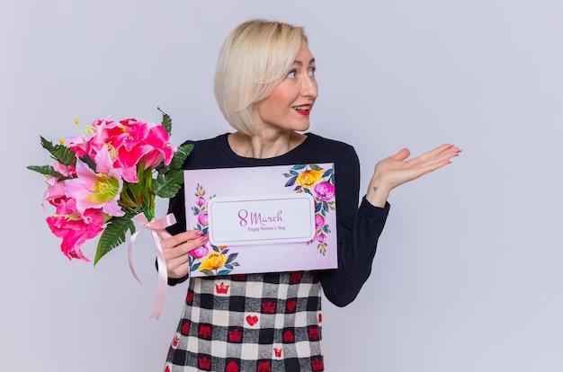 Mulher jovem feliz segurando um cartão e um buquê de flores olhando de lado, apresentando algo com um braço sorrindo, comemorando a marcha do dia internacional da mulher