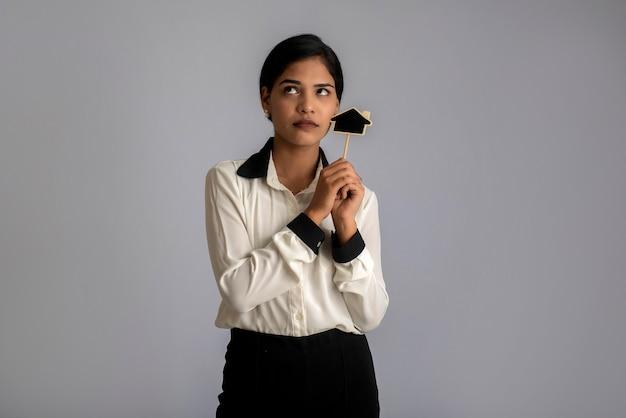 Mulher jovem feliz segurando uma pequena placa de recorte de casa nas mãos em uma parede cinza.