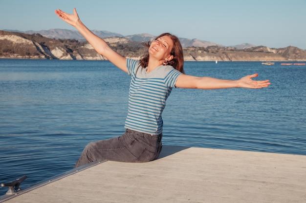 Mulher jovem feliz sentada em um píer em um lago e se divertindo com a água garota espirra água na natureza conceito de relaxamento e uma vida feliz