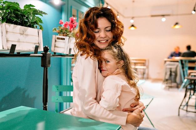 Mulher jovem feliz sentada no café com sua garotinha encantadora e abraçando-a