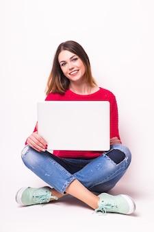 Mulher jovem feliz sentada no chão com as pernas cruzadas e usando o laptop na parede cinza