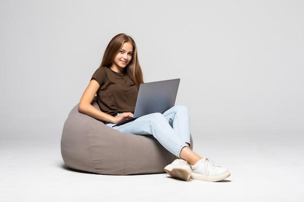 Mulher jovem feliz sentada no chão usando o laptop na parede cinza