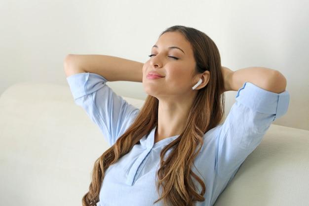 Mulher jovem feliz sentada ouvindo música com fones de ouvido sem fio em seu telefone celular em casa enquanto ela relaxa com os olhos fechados em um sofá.