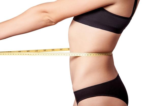 Mulher jovem feliz slim fit com fita métrica, medindo a cintura com calcinha preta, isolada no fundo branco. tiro do estúdio.
