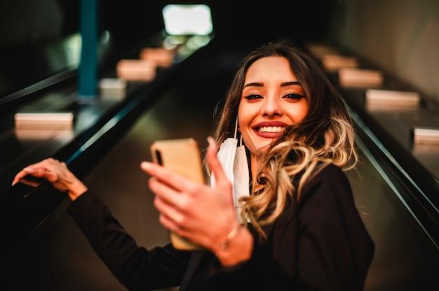 Mulher jovem feliz sobe as escadas rolantes com o telefone celular.