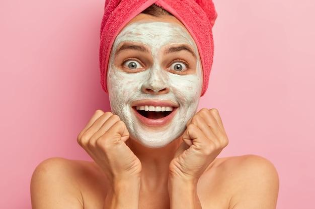 Mulher jovem feliz sorri amplamente, mantém as duas mãos sob o queixo, não consegue acreditar no que está vendo, aplica máscara de argila, tem expressão facial alegre