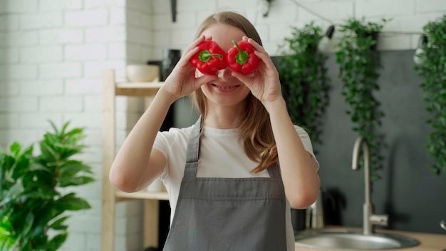 Mulher jovem feliz sorri e se diverte brincando com pimenta vermelha na frente dos olhos na cozinha da casa