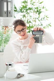 Mulher jovem feliz sorridente em copos com calculadora no escritório. equilíbrio de sucesso.