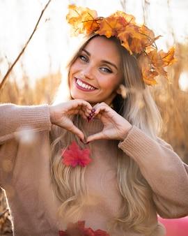 Mulher jovem feliz sorrindo e fazendo formato de coração com a mão no exterior