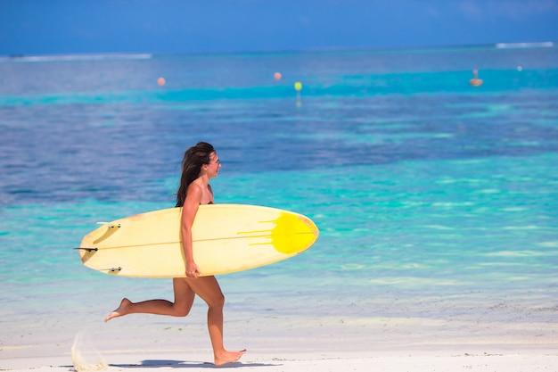 Mulher jovem feliz surf runing na praia com uma prancha de surf