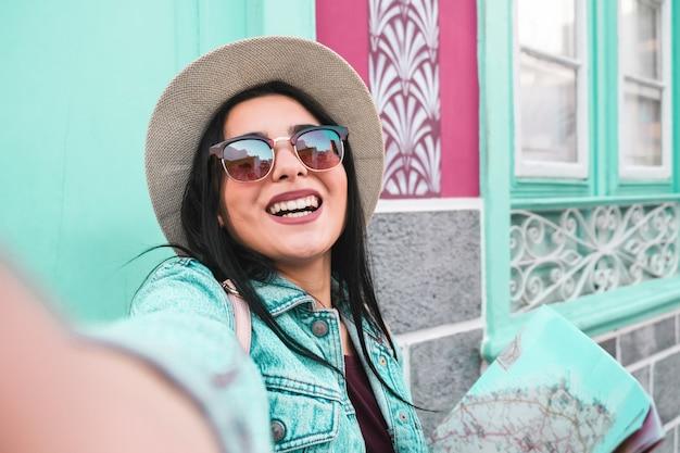 Mulher jovem feliz, tirando fotos e vídeos com a câmera do smartphone