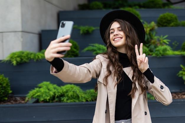Mulher jovem feliz tirando uma selfie com o símbolo da paz na rua da cidade