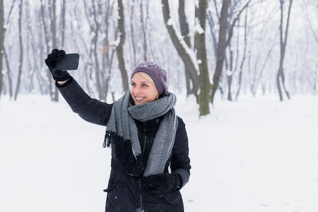 Mulher jovem feliz tomando selfie na floresta durante o inverno
