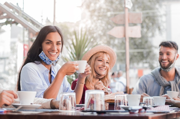 Mulher jovem feliz usando máscara e sorrindo no restaurante