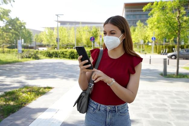 Mulher jovem feliz usando máscara facial ffp2 kn95 na rua da cidade segurando um smartphone