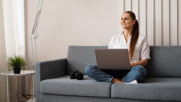 Mulher jovem feliz usando o laptop em casa. no sofá ao lado da mulher está uma câmera. o fotógrafo retoca as fotos em casa.