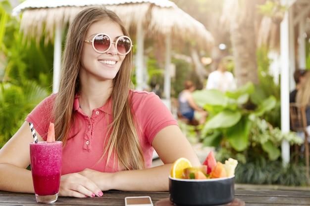 Mulher jovem feliz usando óculos de sol redondos da moda e camisa pólo, aproveitando as férias, tendo batido de frutas frescas no café.