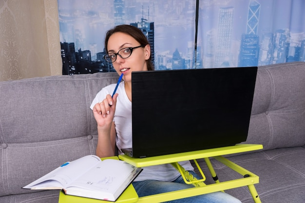 Mulher jovem feliz usando óculos olhando atrás do laptop enquanto trabalhava e fazia seus negócios em casa segurando uma caneta