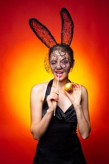Mulher jovem feliz usando orelhas de coelho e ovos de páscoa. fato de orelhas de coelho coelhinho.