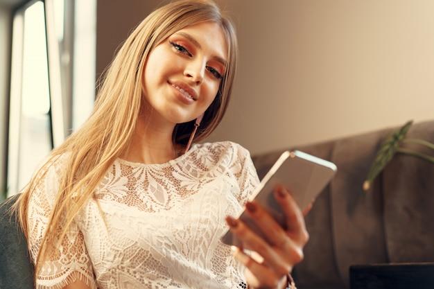 Mulher jovem feliz usando seu smartphone enquanto está sentado na cantina