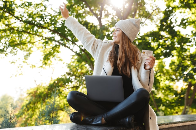 Mulher jovem feliz vestida com um casaco e chapéu outono sentada ao ar livre, usando um computador laptop, mostrando um cartão de crédito de plástico