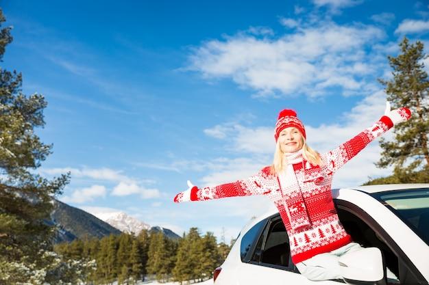 Mulher jovem feliz viajar de carro nas férias de inverno. conceito de estilo de vida ativo e saudável