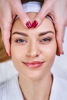 Mulher jovem feliz visitando o salão de beleza para relaxar e receber massagem facial contra futuras rugas