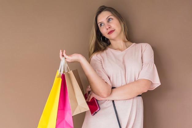 Mulher jovem, ficar, com, bolsas para compras, e, smartphone
