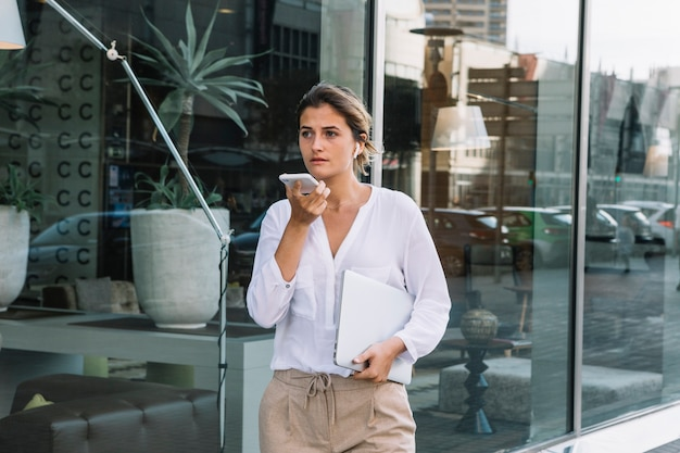 Mulher jovem, ficar, em, a, edifício escritório, entrada, usando, comando voz, registrador