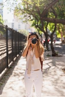 Mulher jovem, ficar, em, a, parque, levando, foto, de, câmera