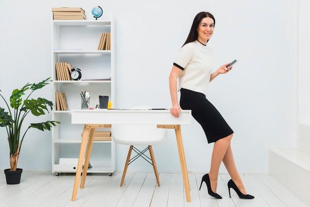 Mulher jovem, ficar, em, escritório, com, smartphone