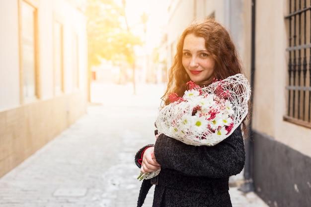 Mulher jovem, ficar, em, rua, com, flores