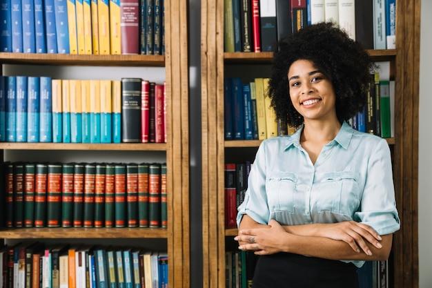 Mulher jovem, ficar, perto, estante de livros, em, escritório