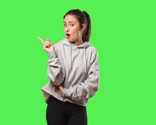 Mulher jovem fitness apontando para o lado