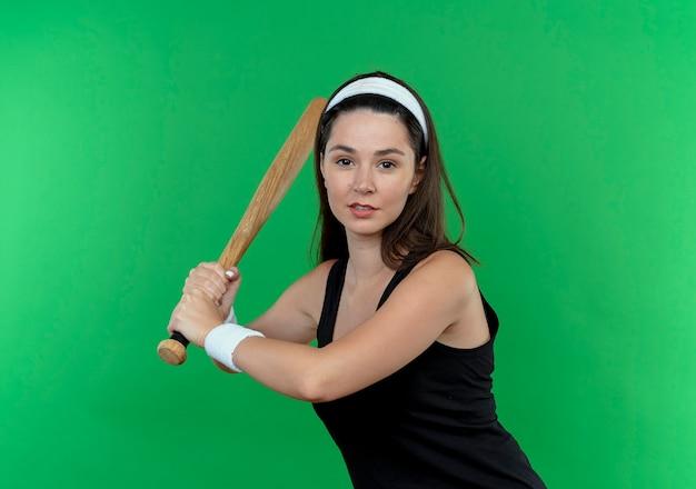 Mulher jovem fitness balançando taco de beisebol com tiara, parecendo confiante em pé sobre um fundo verde