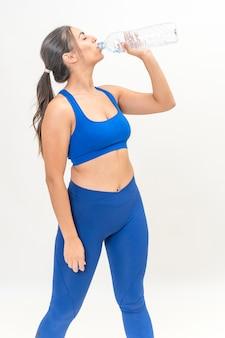 Mulher jovem fitness bebendo de uma garrafa de água, vestida com roupas esportivas