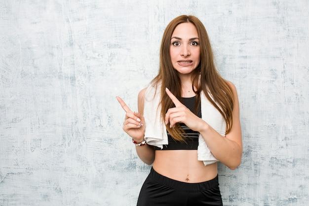 Mulher jovem fitness chocado apontando com o dedo indicador para um espaço de cópia.