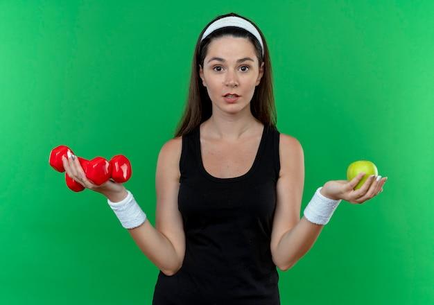 Mulher jovem fitness com bandana e fones de ouvido segurando halteres e maçã verde olhando para a câmera confusa em pé sobre fundo verde
